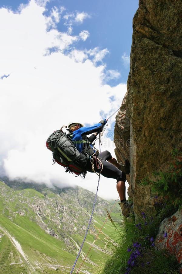 The climber climbs the rock by the rope. royalty free stock photography