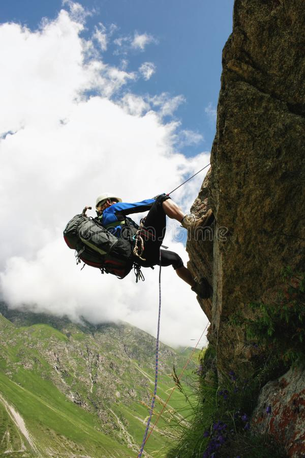 The climber climbs the rock by the rope. royalty free stock image