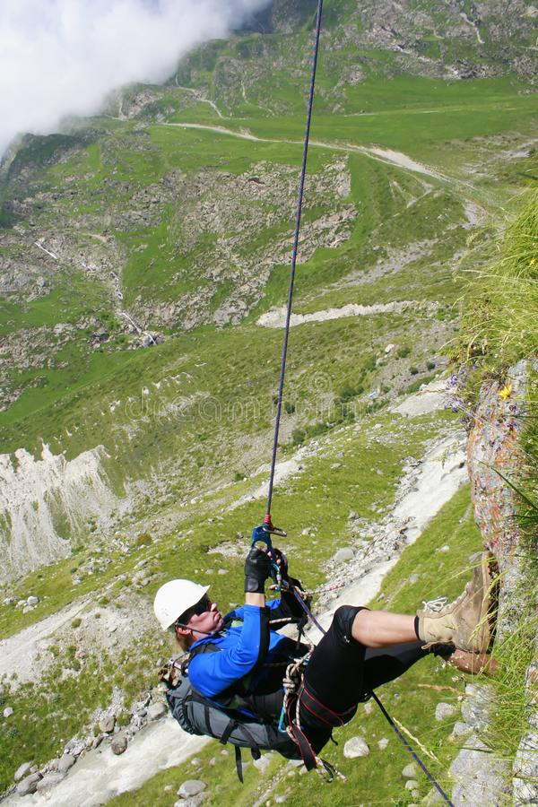 The climber climbs the rock by the rope. stock images