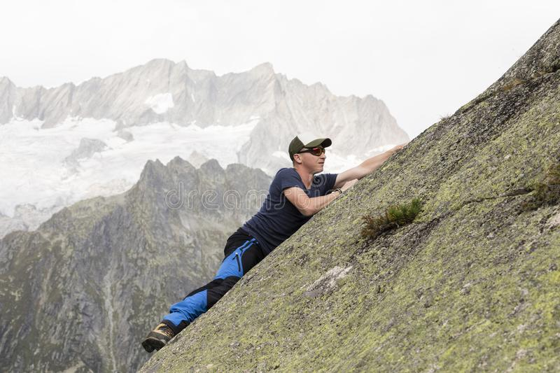 Climber climbs on a sloping rock wall in the Swiss mountains stock photography