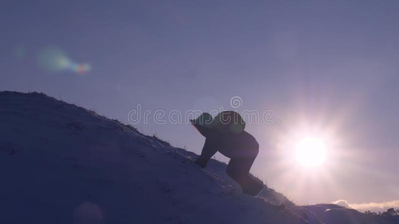 Climber climbs snowy mountain in rays of bright sun. tourist makes climb to top on background of beautiful sky. man stock photo