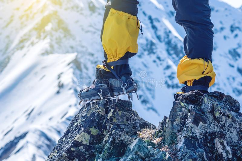 Climber in crampons stands on the rocks in front of the entrance to the peak on the background of the snowy mountains. royalty free stock photos