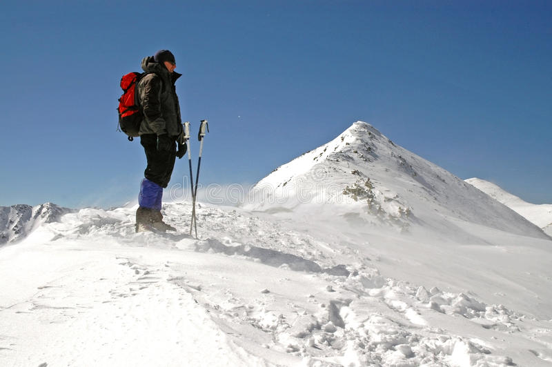 Climber facing wind and snow on the mountain royalty free stock photography