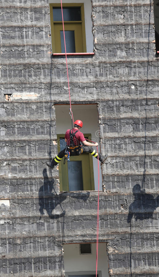 climber firefighter rappelling the wall during the fire drill royalty free stock image