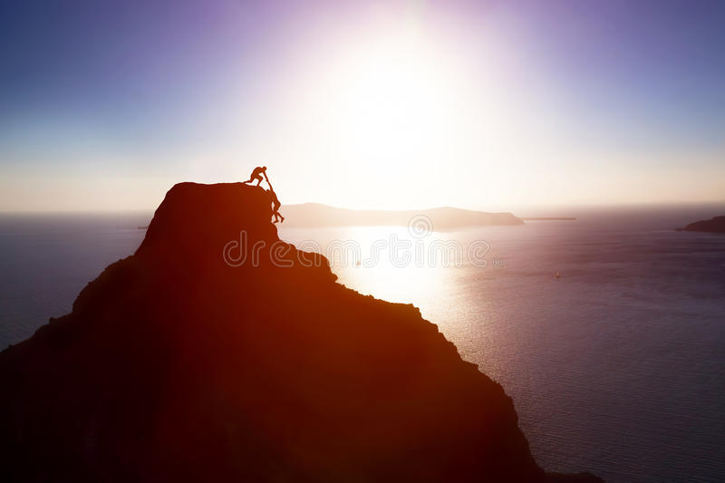 Climber giving hand and helping his friend to reach the top of the mountain. Help, support stock photography