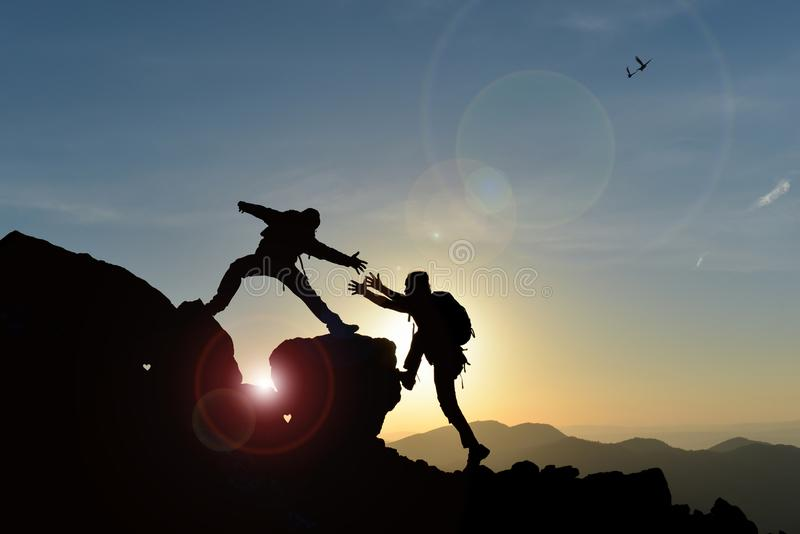 Climber giving a hand to another stock images