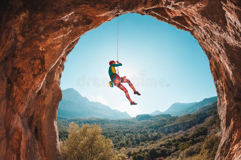 The climber is hanging on a rope stock image