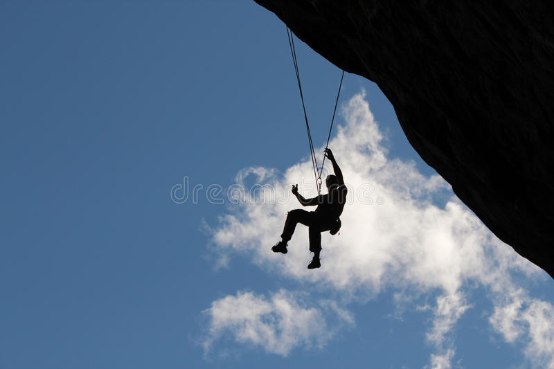 Climber hanging from rope stock images