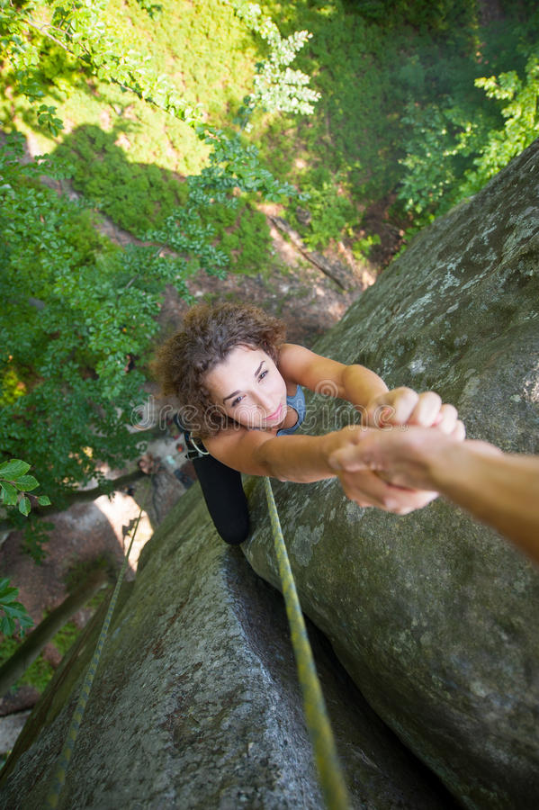 Climber helping female climber to reach a peak of mountain royalty free stock photo