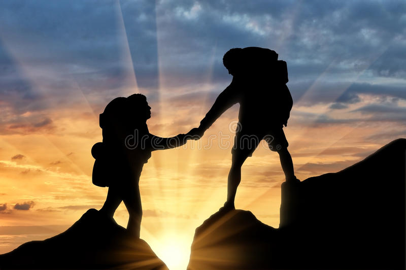 Climber helps another climber sunset. Mountaineer gives helping hand to another alpinist while climbing up on sunset. Concept mountaineering royalty free stock photos