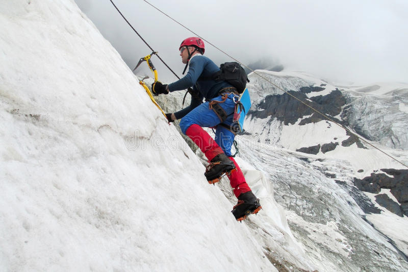 Climber with ice axes. On snow alpinist route, rocky mountain peaks and glacier. Alpinist with equipment - ice axe, crampons and rope. Beautiful scenery royalty free stock photos
