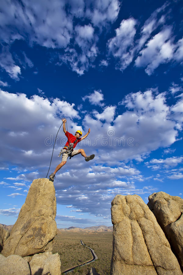 Climber jumping across gap. royalty free stock images
