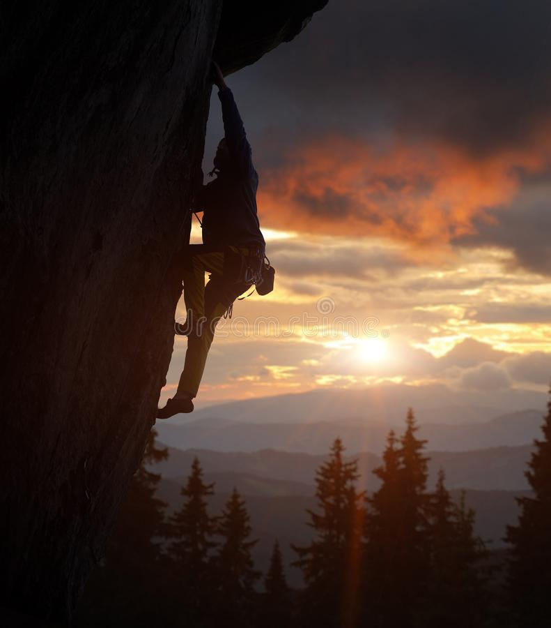 Climber male silhouette rock climbing on cliff in nightfall. Mountains view, amazing sunset sky. Side view. Copy space royalty free stock photography