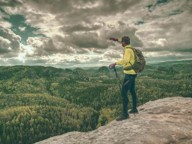 Climber man with backpack and trekking clothes on the top royalty free stock images