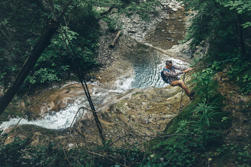 Climber Man Climbs The Hill On Waterfall Background Hiking Mountain Adventure Concept. Young climber climbs to the top of the hill with a rope, waterfall royalty free stock photos