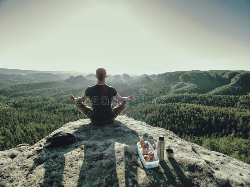 Climber man sit on rock, prepare for eating snack during rest. From extreme rock climbing, young, adult, water, bottle, toil, thermos, summer, success, sports royalty free stock images