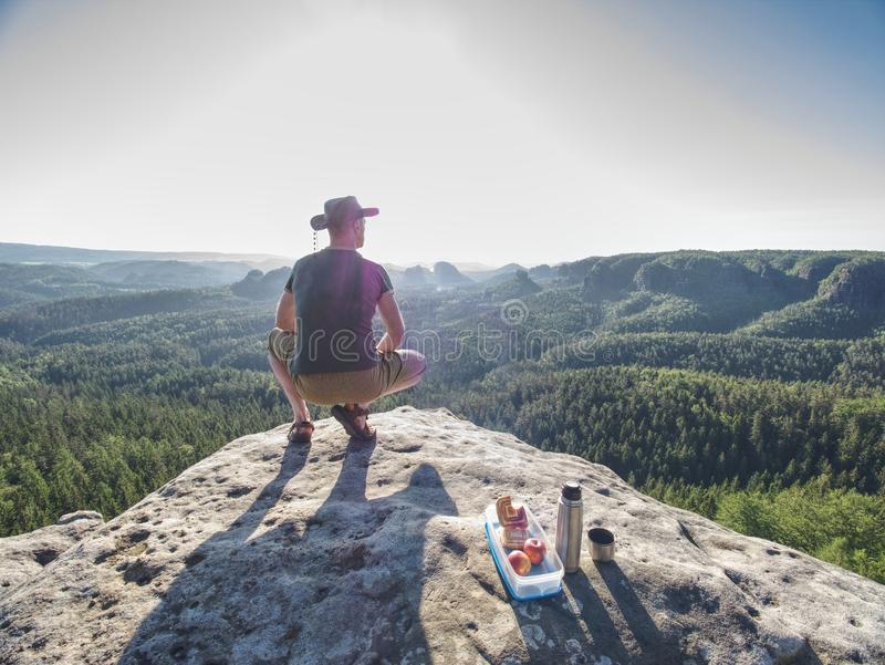 Climber man sit on rock, prepare for eating snack during rest. From extreme rock climbing, young, adult, water, bottle, toil, thermos, summer, success, sports stock photo