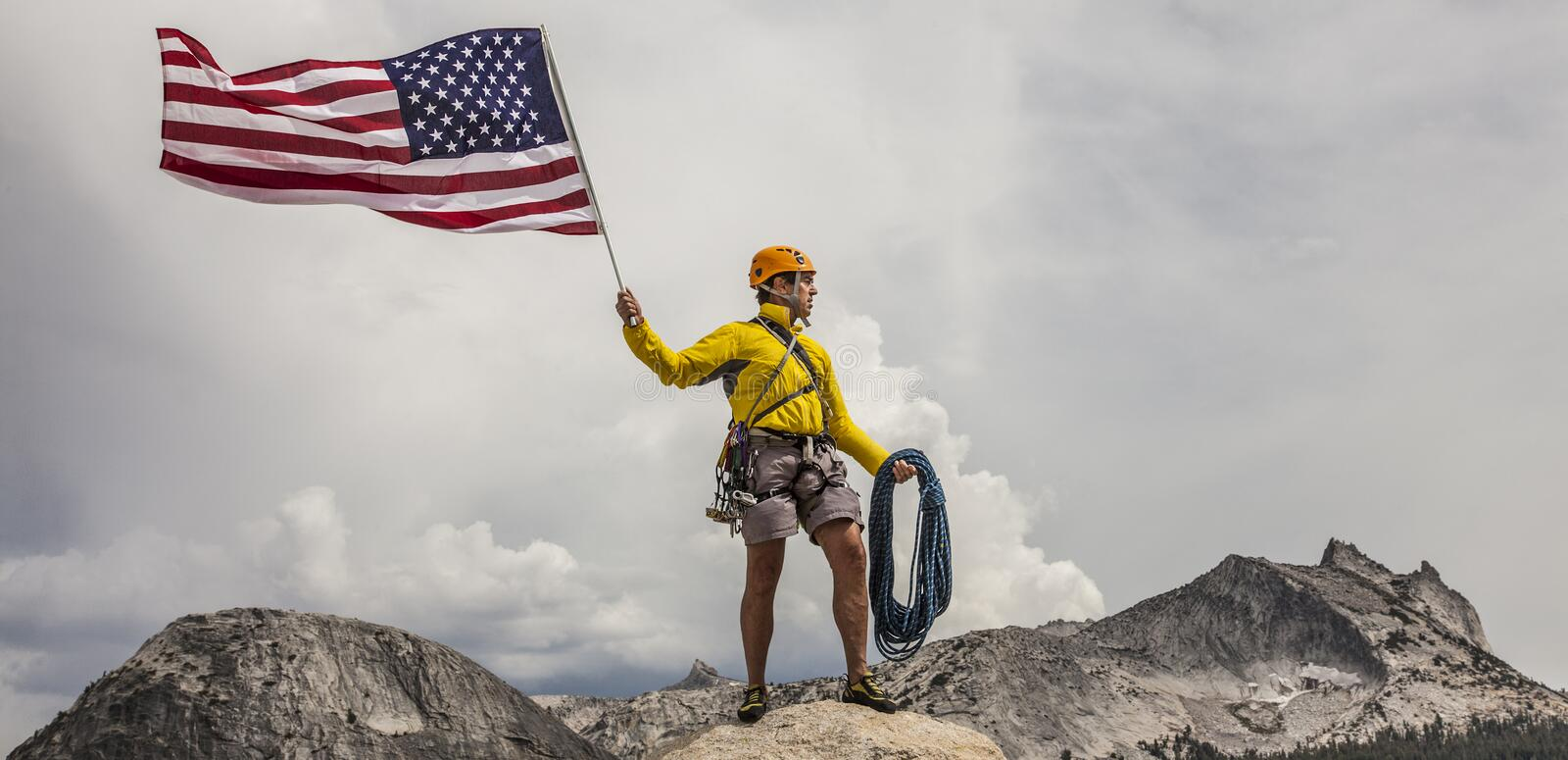 Climber raising the flag on the summit. royalty free stock image