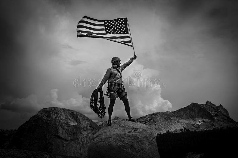 Climber raising the flag on the summit. Climber waves an American Flag from the summit after a challenging ascent royalty free stock photos