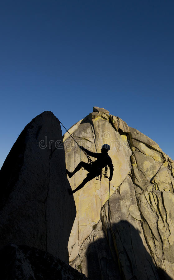 Climber rappelling from the summit. royalty free stock photography