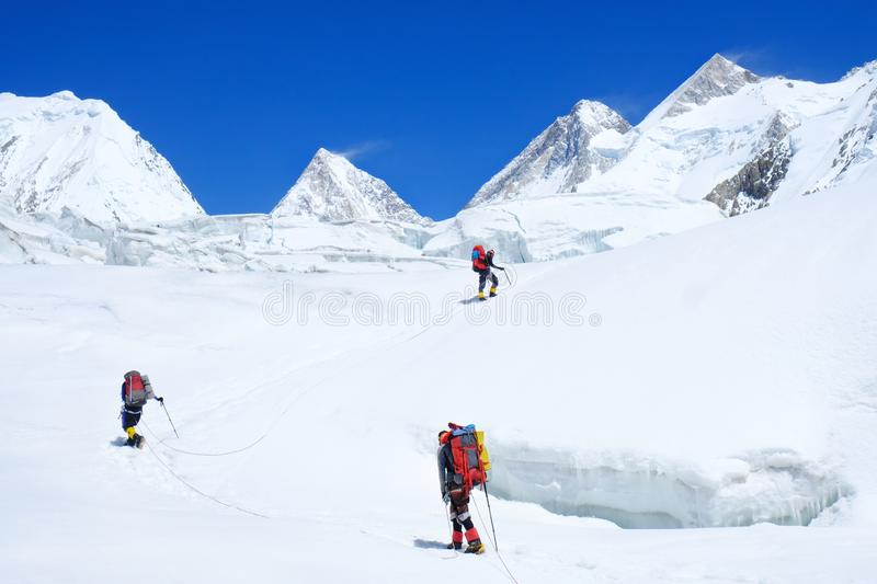 Climber reache the summit of mountain peak. Three climber on the glacier. Success, freedom and happiness, achievement in mountains stock images