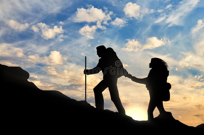 Climber reaches out to his partner by helping each other. Climber helps partner together to reach the summit. concept of teamwork and help stock photography
