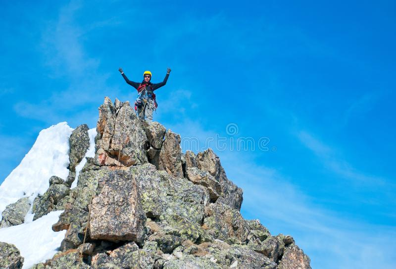 Climber reaches the summit of mountain peak. Success, freedom and happiness, achievement in mountains. Climbing sport concept. stock photo