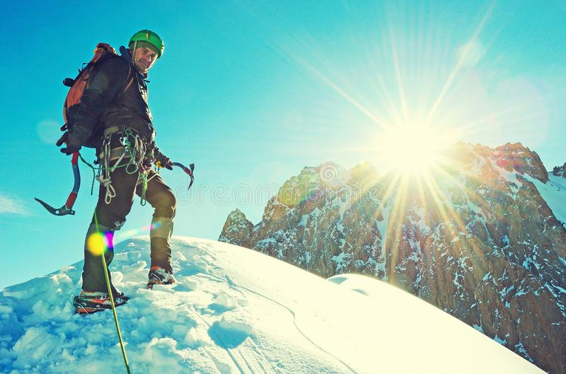 Climber reaches the summit of mountain peak. Success, freedom and happiness, achievement in mountains. Climbing sport concept. royalty free stock images