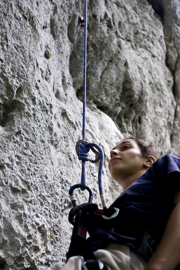 Climber resting. Young woman climber resting as she hangs by her rope while ascending a rocky steep wall royalty free stock photos
