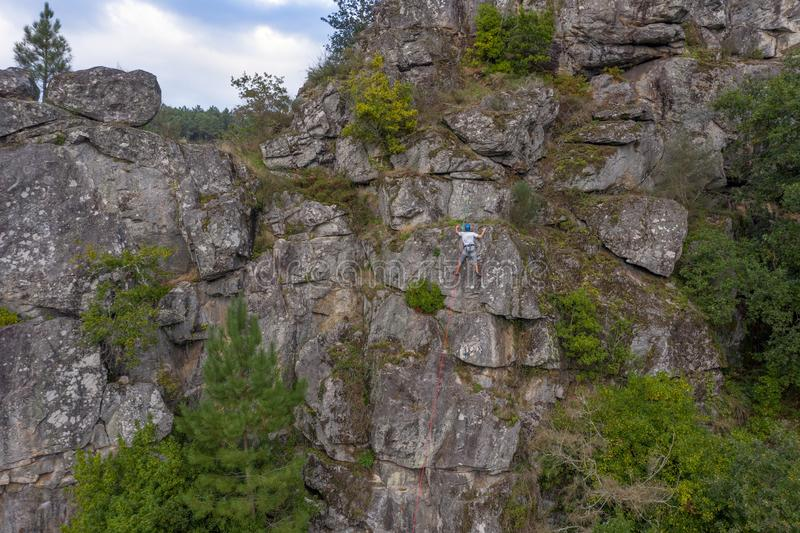 Climber on a safety rope climbs a cliff aerial view stock photography