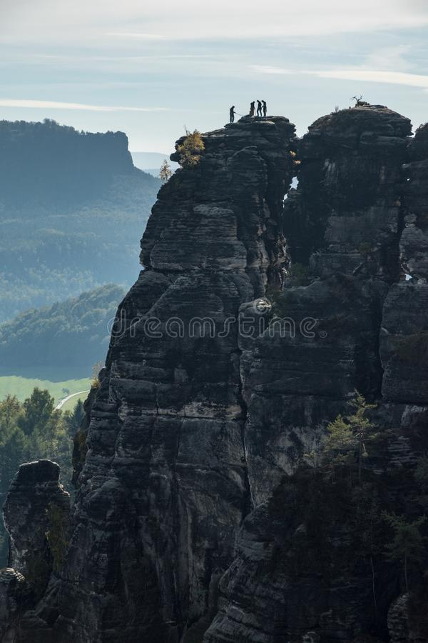 Climber silhouettes on a sandstone tower in Saxon Switzerland National Park, Germany royalty free stock photo