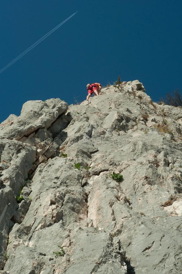 Climber in the sky. Climbing on a sunny summer day royalty free stock image