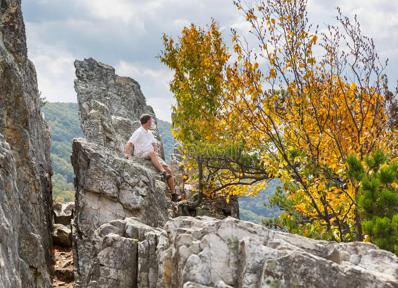 Climber on top of Seneca Rocks. Senior climber reaches the summit of the rocky granite mountain top of Seneca Rocks in West Virginia royalty free stock photos