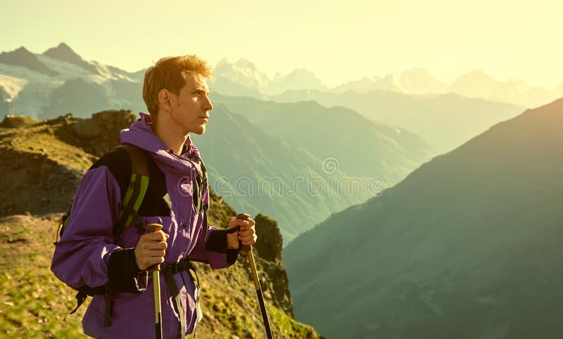 Climber on trail in the mountains. a man with backpack in a hike royalty free stock image