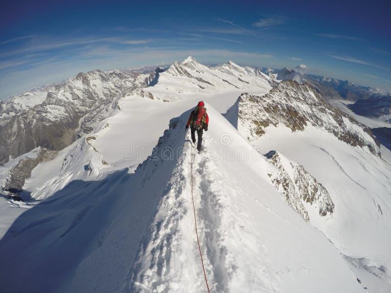 Climber walking on extremely sharp ridge stock photos