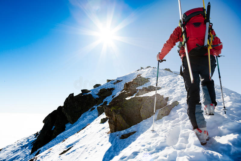 Climberr die langs een steile sneeuwrand met de skis in t naar boven gaan royalty-vrije stock afbeeldingen