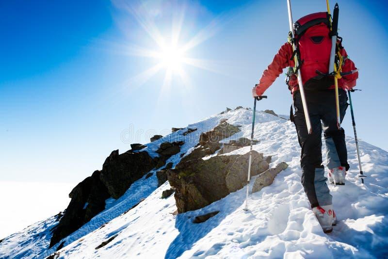 Climberr que camina para arriba a lo largo de un canto nevoso escarpado con los esquís en t imágenes de archivo libres de regalías