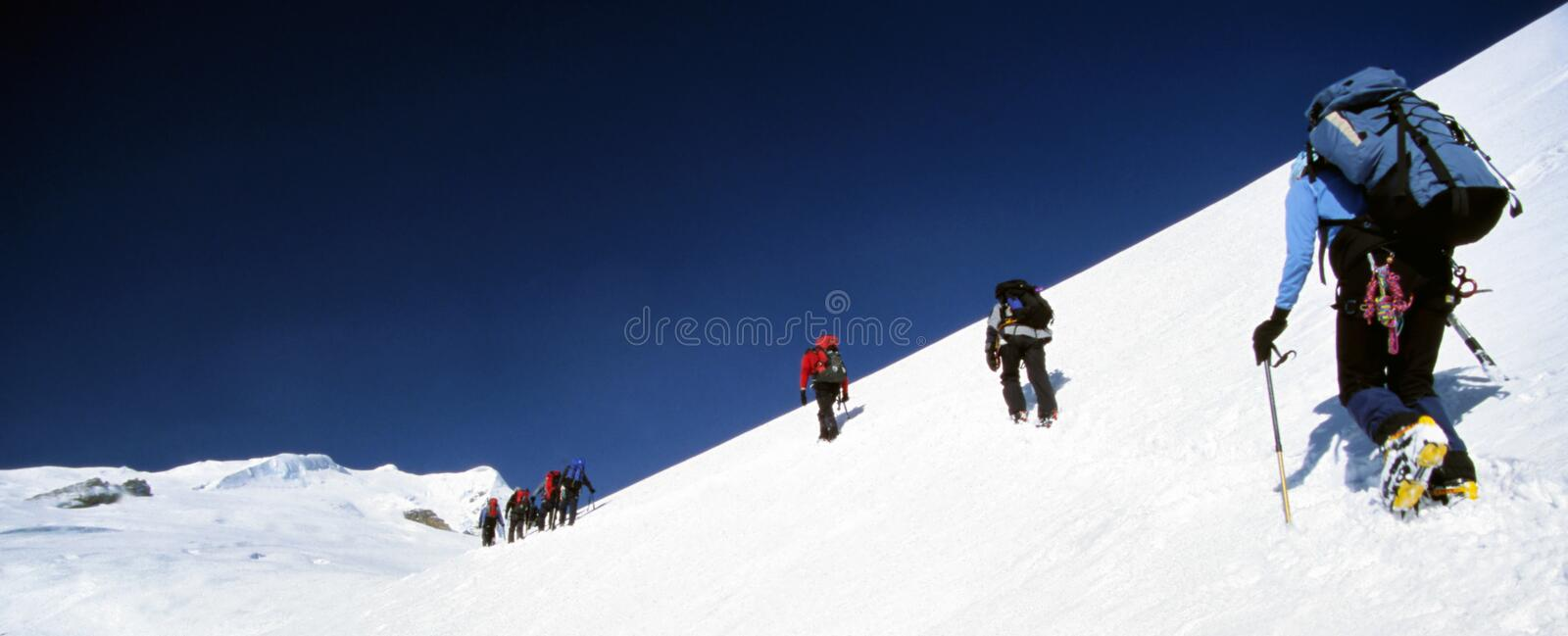 Climbers. Making a high glacial traverse towards their summit goal stock photo