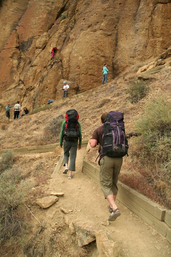 Climbers approaching rock face stock photo