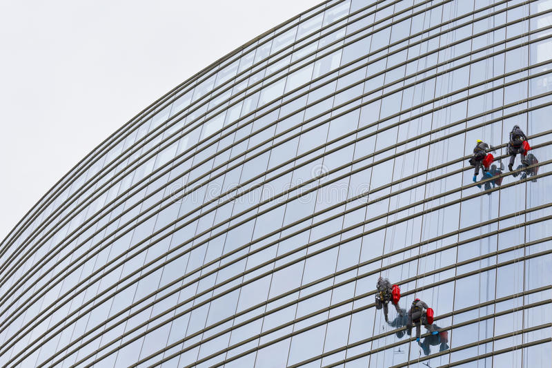 Climbers 6. Climbers on clean glass skyscraper stock image