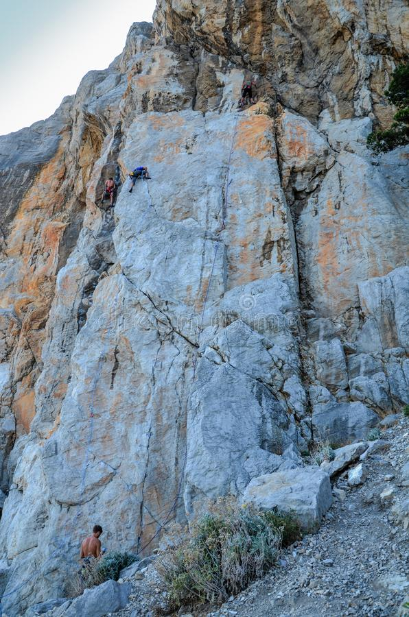 Climbers climb up the steep cliff stock photo