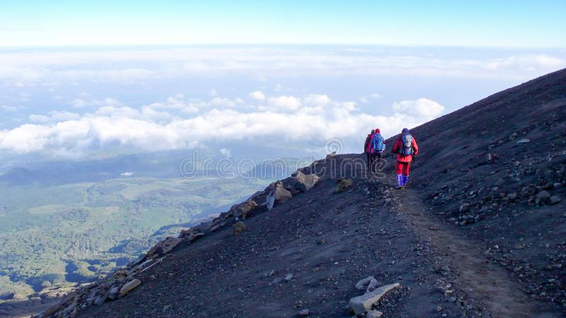 Climbers hike down from the summit of Mount Meru in Arusha National Park in Tanzania. Arusha National Park, Kilimanjaro Province / Tanzania - 1. January 2016 royalty free stock photo