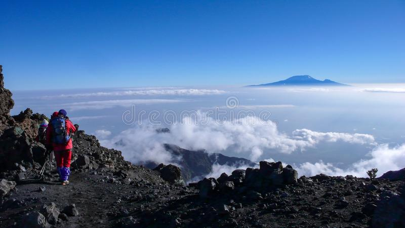 Climbers hike down from the summit of Mount Meru in Arusha National Park in Tanzania. Arusha National Park, Kilimanjaro Province / Tanzania - 1. January 2016 stock photography