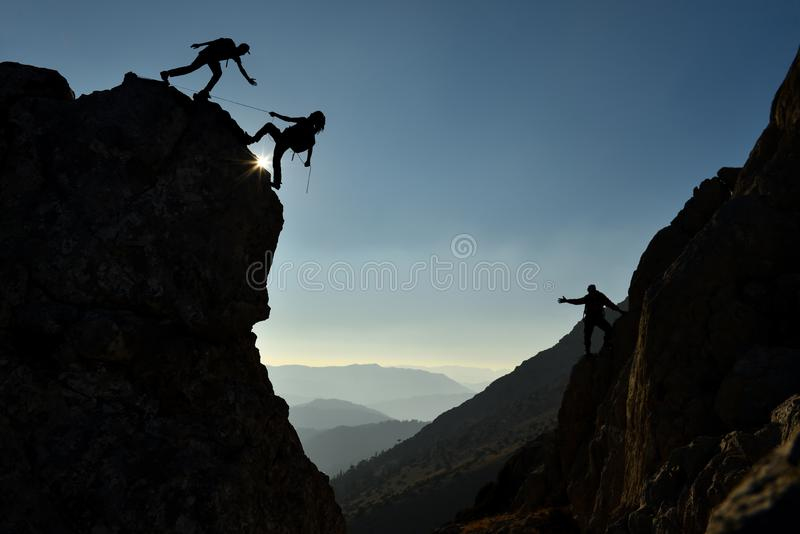 Climbers on mountain side. A trio of climbers on a mountain side royalty free stock images