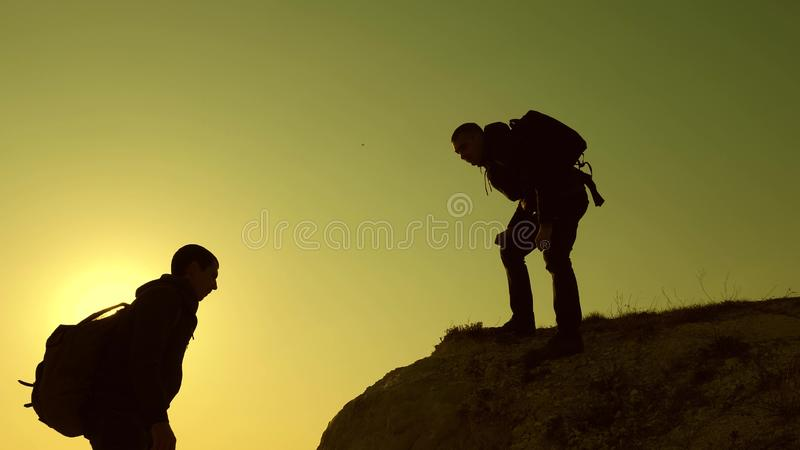 Climbers silhouettes stretch their hands to each other, climbing to top of hill. teamwork of business people. travelers stock photography