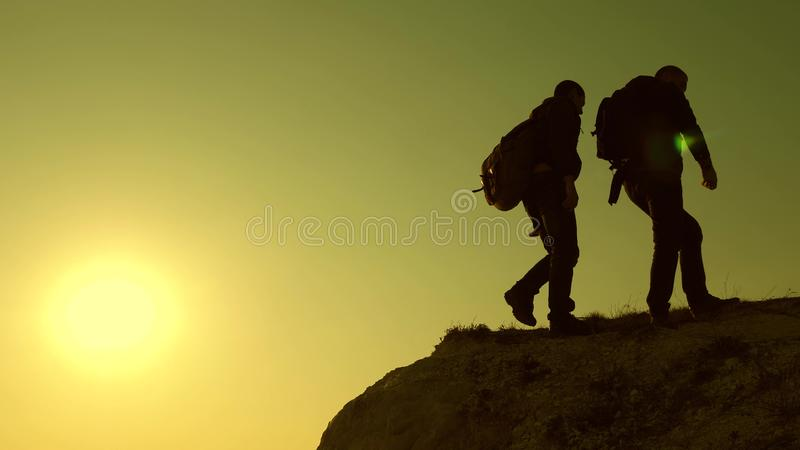 Climbers silhouettes stretch their hands to each other, climbing to top of hill. teamwork of business people. travelers stock images