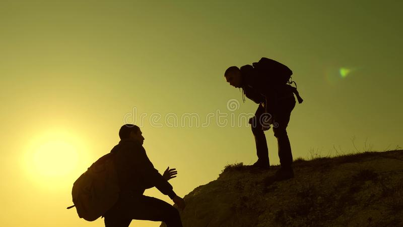 Climbers silhouettes stretch their hands to each other, climbing to top of hill. teamwork of business people. travelers royalty free stock photography