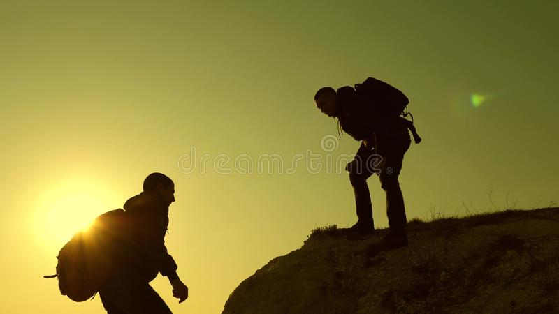 Climbers silhouettes stretch their hands to each other, climbing to top of hill. teamwork of business people. travelers stock photos