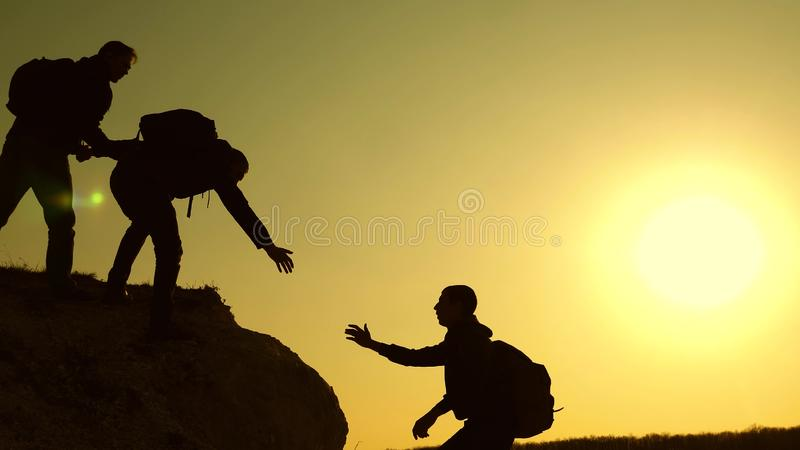 Climbers silhouettes stretch their hands to each other, climbing to the top of the hill. travelers climb one after stock photography