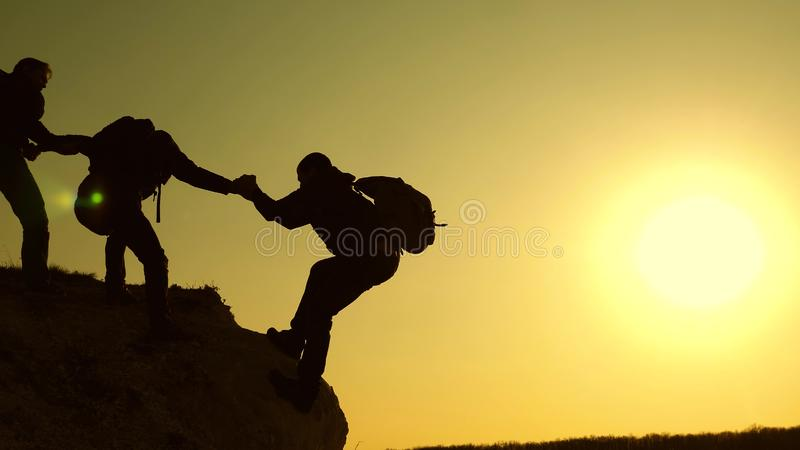 Climbers silhouettes stretch their hands to each other, climbing to the top of the hill. travelers climb one after royalty free stock image